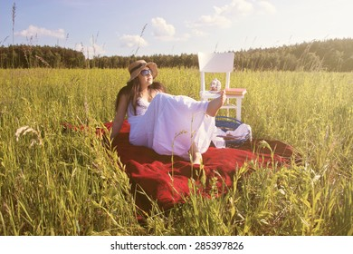 Woman with Hat in White Dress is Sitting on Red Cloth on Green Meadow with WHite Chair and Picnic Basket