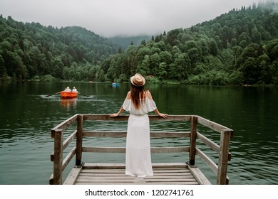 The woman with hat and white dress standing against lake in nature