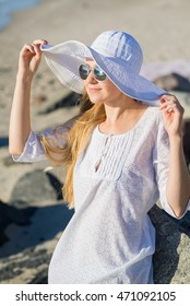 Woman in hat and white tunic sitting on the beach.
