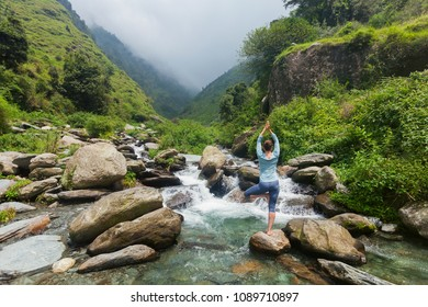 Woman in Hatha yoga balance yoga asana Vrikshasana tree pose at waterfall outdoors