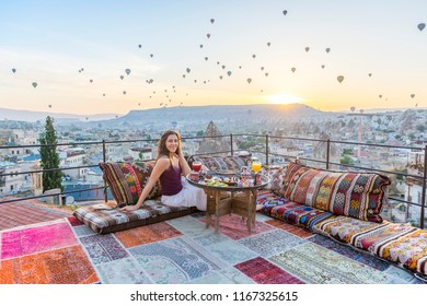 A woman have breakfast on one of the Cappadocia roof in early morning sunrise, when balloons fly. Romantic scene Cappadocia, Turkey.