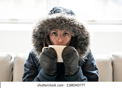 Woman have cold drink coffee on the sofa at home with winter coat