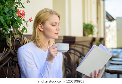 Woman have drink cafe terrace outdoors. Find opportunity to read more. Girl drink coffee while read bestseller book by popular author. Mug coffee and interesting book best combination perfect weekend.