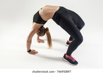 Woman have elastic spine. Bridge pose. Athletic woman doing yoga. Studio shot, gray background