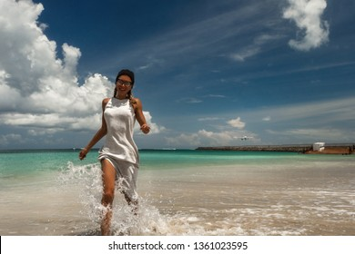 Woman have fun on the beach against of the landing airplane on Bali island, Jimbaran. Traveling on an airplane concept. Text space.