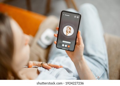 Woman have a high heart rate, call a doctor while sitting on sofa at home. Health and wellness concept. Focus on phone screen.