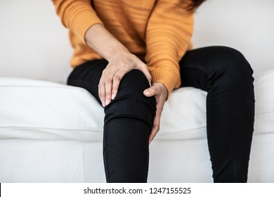 woman have a kneecap pain sitting on sofa feeling so illness,Healthcare concept