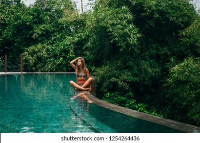 Woman have a rest and chill in the pool with amazing view on the jungle