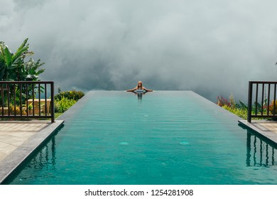 Woman have a rest and chill in the pool with amazing view on the jungle. Happy girl on the vacation