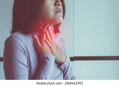 Woman have a sore throat,Women touching her neck with hands,Health care Concept