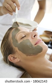 woman havin mud mask applied to her face by professional