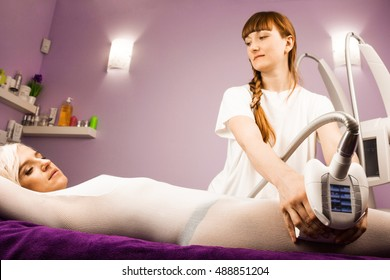 Woman having anti cellulite massage with therapist and apparatus
