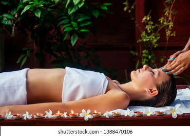 Woman having ayurveda spa treatment in asia salon head, hair and face massage shirodhara candles and flowers on the background