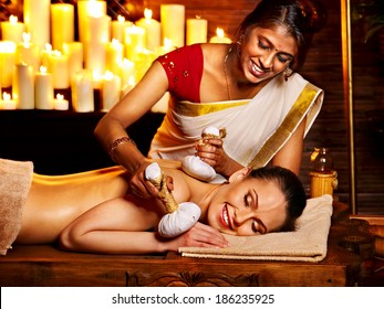 Woman having ayurvedic massage with pouch of rice.