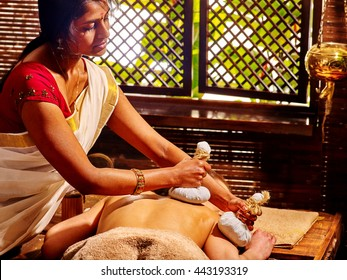 Woman having ayurvedic massage with pouch of rice. Passage to massage India