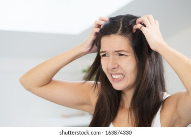 Woman having a bad hair day grimacing in disgust as she looks in the mirror and runs her hands through her hair