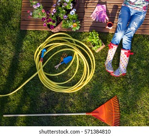 Woman having break while working in the garden, gardening tools around.