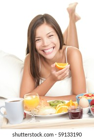 Woman having breakfast in bed. Big toothy smile. Caucasian / asian woman isolated on white background