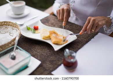 A woman is having breakfast at a restaurant.