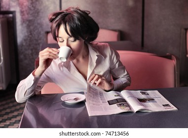 Woman having breakfast while reading a newspaper in a bar
