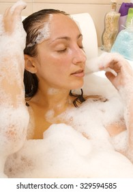 Woman having a bubble bath. Close eyes, close up portrait