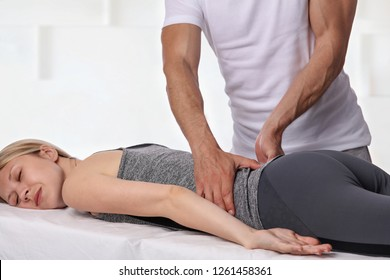 Woman having chiropractic back adjustment. Osteopathy, Physiotherapy, sport injury rehabilitation concept, holistic care