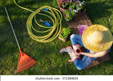 Woman having a coffee break while working in the garden, gardening tools around.