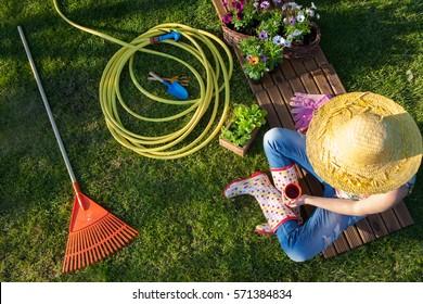 Frauen, die eine Kaffeepause haben, während sie im Garten arbeiten, Gartenwerkzeuge herum.
