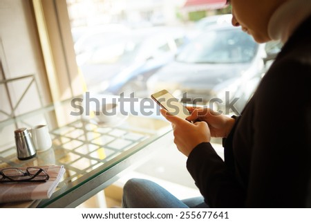 Woman having a coffee and chatting with her touch screen smart phone