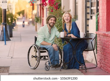 Woman having coffee with friend in wheelchair on sidewalk