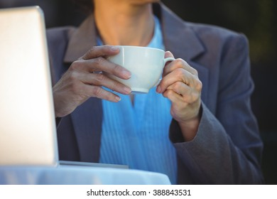 Woman having coffee using her laptop in a restaurant
