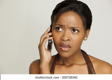 Woman having a conversation on her phone, looking anxious.