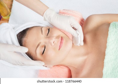Woman is having cosmetic treatment at spa salon. Cosmetologist medical gloves is touching girl's face.