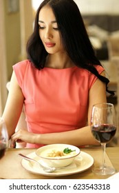 Woman having dinner in restaurant. Portrait of girl in red dress eating and drinking red wine