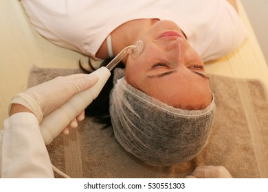Woman having disinfection on face in beauty salon.