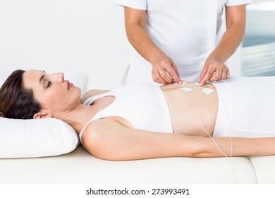 Woman having electrotherapy on white background