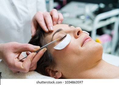 woman having eye lashes tinted in beauty salon