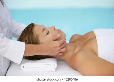 Woman having face massage by a swimming pool