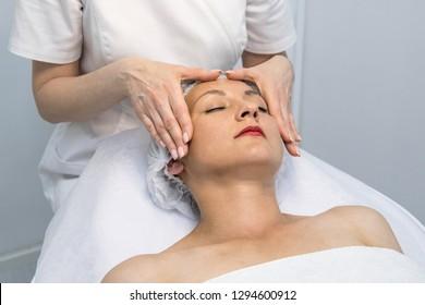 Woman having a face treatment in a beauty salon. Face massage.