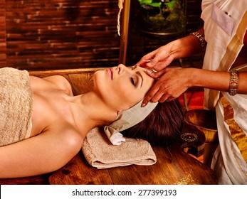 Woman having facial  ayurveda spa treatment. Wooden brown bed