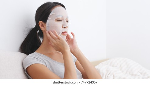 Woman having facial mask on bed