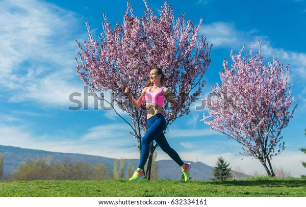 Woman having fitness run in the spring sun