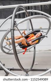 Woman having fun at the astronaut training gyroscope swing