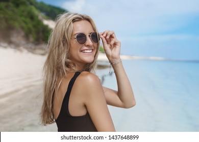 Woman having fun enjoy summer vacation booked tickets best bali hotel walk sandy beach sunbathing wear sunglasses turn camera smiling joyful contemplating blue calm ocean view, travelling sea