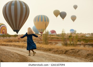 Woman Having Fun With Flying Hot Air Balloons On Background