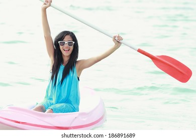 woman having fun kayaking on a sunny day at the beach