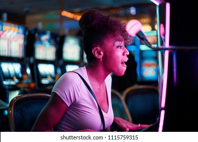 woman having fun playing slot machine at casino