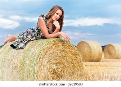Woman having fun sitting on hay bale