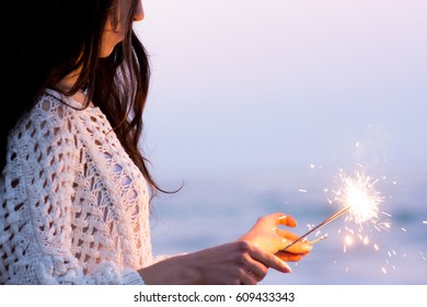 Woman having fun with sparklers near the sea at the evening