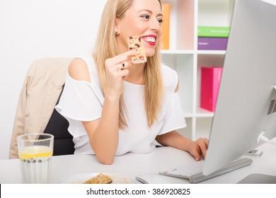 Woman having granola bar while working